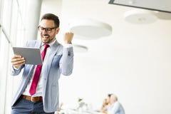 Hombre de negocios feliz con la tableta en oficina Foto de archivo