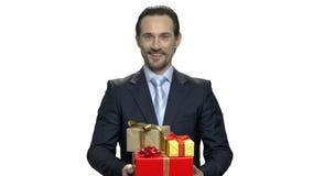 Hombre de negocios feliz con las cajas de regalo festivas metrajes