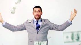 Hombre de negocios feliz con los paquetes de dinero del dólar almacen de video