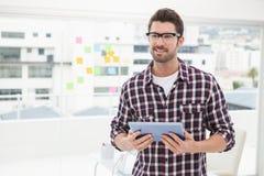 Hombre de negocios feliz con los vidrios que sostienen la tableta Imágenes de archivo libres de regalías
