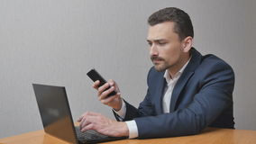 Hombre de negocios feliz con un ordenador portátil y Smartphone almacen de video
