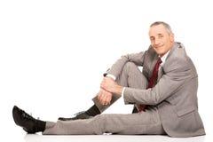 Hombre de negocios feliz de la vista lateral que se sienta en el piso Imagen de archivo
