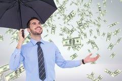 Hombre de negocios feliz debajo del paraguas que mira la lluvia del dinero contra el fondo blanco Imagen de archivo
