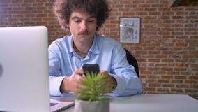 Hombre de negocios feliz del empollón que trabaja en el ordenador portátil y que toma el teléfono, animándolo y sentándose en ofi metrajes