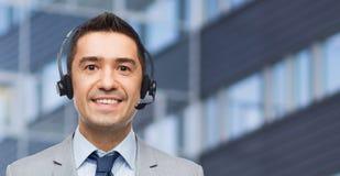 Hombre de negocios feliz en auriculares sobre centro de negocios Foto de archivo
