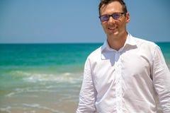 Hombre de negocios feliz en camisa con un ordenador portátil y con los vidrios que camina en la playa imagenes de archivo