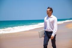 Hombre de negocios feliz en camisa con un ordenador portátil y con los vidrios que camina en la playa foto de archivo libre de regalías