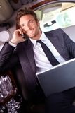 Hombre de negocios feliz en llamada de teléfono en limusina Foto de archivo libre de regalías
