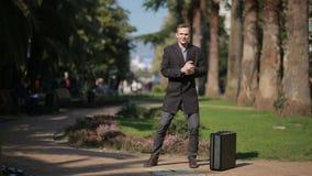 Hombre de negocios feliz en una capa y con una maleta que baila feliz al aire libre contra un contexto de palmeras metrajes