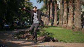 Hombre de negocios feliz en una capa y con una maleta que baila feliz al aire libre contra un contexto de palmeras almacen de video
