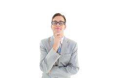 Hombre de negocios feliz Geeky que piensa con la mano en la barbilla imagen de archivo libre de regalías