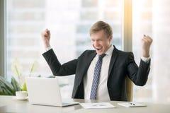 Hombre de negocios feliz joven en el escritorio foto de archivo