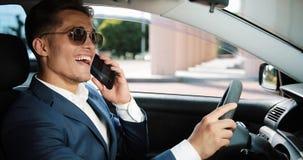 Hombre de negocios feliz joven que habla en el smartphone que se sienta dentro del coche Negocio, gente, comunicación, éxito y fi almacen de video