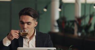 Hombre de negocios feliz joven que se sienta en el funcionamiento acogedor del café con el ordenador portátil y el té de consumic almacen de metraje de vídeo