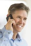 Hombre de negocios feliz Looking Away While que usa el teléfono móvil Imagen de archivo libre de regalías