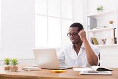 Hombre de negocios feliz negro feliz en la oficina, trabajo con el ordenador portátil, vidrios que llevan fotografía de archivo