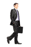 Hombre de negocios feliz que celebra una cartera y caminar Foto de archivo