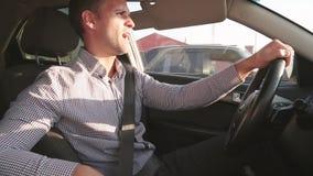 Hombre de negocios feliz que conduce un coche moderno y que canta almacen de video