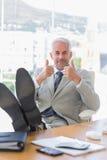 Hombre de negocios feliz que da los pulgares para arriba con los pies para arriba Fotos de archivo libres de regalías
