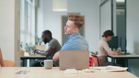 Hombre de negocios feliz que da vuelta alrededor en silla en el espacio coworking almacen de video