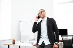 Hombre de negocios feliz que habla en el teléfono celular en oficina foto de archivo libre de regalías