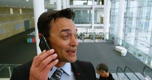 Hombre de negocios feliz que habla en el teléfono mientras que en la escalera móvil 4k almacen de video