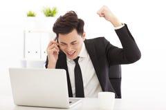 Hombre de negocios feliz que habla en el teléfono en oficina Imágenes de archivo libres de regalías
