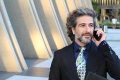 Hombre de negocios feliz que hace una llamada con su smartphone afuera Foto de archivo libre de regalías
