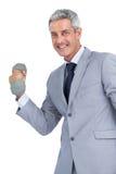 Hombre de negocios feliz que levanta pesas de gimnasia pesadas Imágenes de archivo libres de regalías