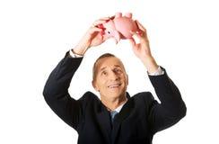 Hombre de negocios feliz que lleva a cabo el piggybank Imagenes de archivo