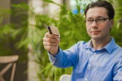 Hombre de negocios feliz que pasa su tarjeta de crédito al camarero en café Hombre de negocios que paga con un crédito o una tarj foto de archivo