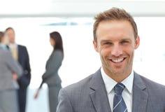 Hombre de negocios feliz que presenta delante de sus personas Fotos de archivo libres de regalías