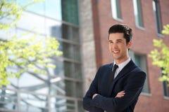 Hombre de negocios feliz que se coloca al aire libre con los brazos cruzados Imágenes de archivo libres de regalías