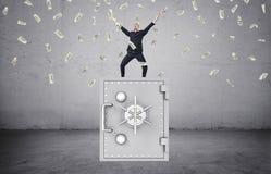 Hombre de negocios feliz que se coloca en la caja fuerte y la porción de dinero en el aire imagen de archivo