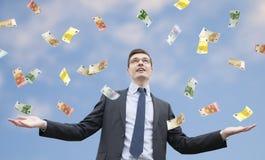 Hombre de negocios feliz que se coloca en la lluvia del dinero foto de archivo