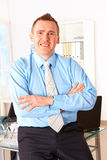 Hombre de negocios feliz que se inclina en el escritorio de oficina imagenes de archivo