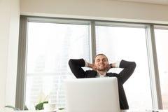 Hombre de negocios feliz que se relaja en el lugar de trabajo en oficina moderna fotografía de archivo libre de regalías