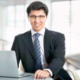 Hombre de negocios feliz que se sienta delante del ordenador portátil Foto de archivo libre de regalías