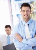 Hombre de negocios feliz que sonríe en oficina Imagenes de archivo