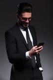 Hombre de negocios feliz que sonríe mientras que manda un SMS Foto de archivo