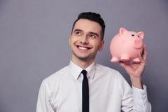 Hombre de negocios feliz que sostiene la caja de dinero del cerdo Imagen de archivo