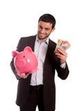 Hombre de negocios feliz que sostiene la hucha con los dólares australianos Imagenes de archivo