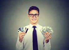 Hombre de negocios feliz que sostiene muchas tarjetas de crédito y efectivo de los billetes de banco del dólar fotografía de archivo libre de regalías