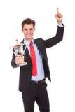 Hombre de negocios feliz que sostiene un trofeo foto de archivo libre de regalías