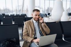 Hombre de negocios feliz que trabaja en el ordenador portátil y que habla en el teléfono móvil en el salón que espera del aeropue fotografía de archivo libre de regalías