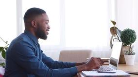 Hombre de negocios feliz que usa el ordenador portátil y relajándose en silla de la oficina almacen de metraje de vídeo
