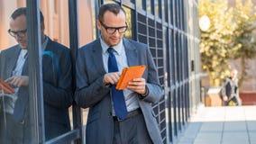 Hombre de negocios feliz que usa la tableta en cubierta anaranjada en un str de la ciudad Fotos de archivo libres de regalías