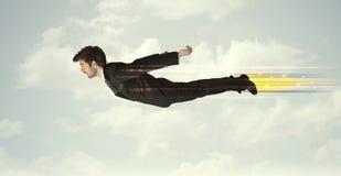 Hombre de negocios feliz que vuela rápidamente en el cielo entre las nubes Foto de archivo