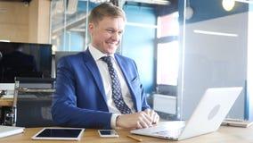 Hombre de negocios feliz Smiling, mientras que trabaja en el ordenador portátil Imágenes de archivo libres de regalías
