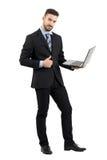 Hombre de negocios feliz sonriente con el ordenador portátil que muestra el pulgar encima del gesto que mira la cámara Fotografía de archivo libre de regalías
